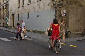 Woman biking down the street in Le Marais, Paris, France