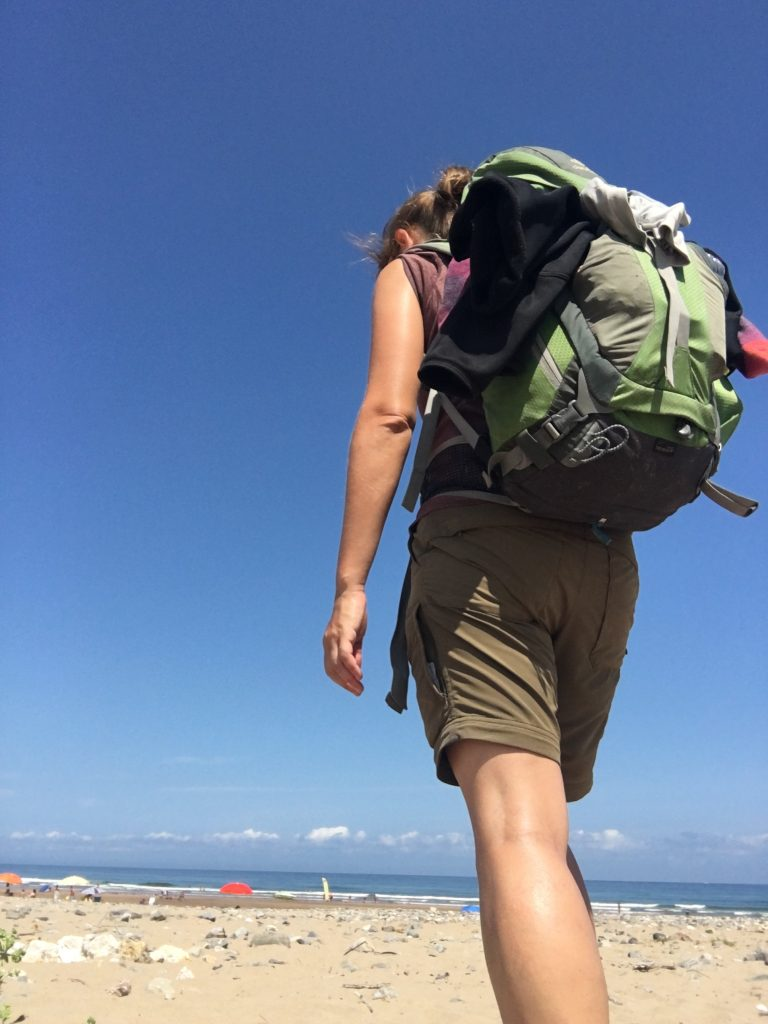Nadine and backpack on beach, Camino del Norte
