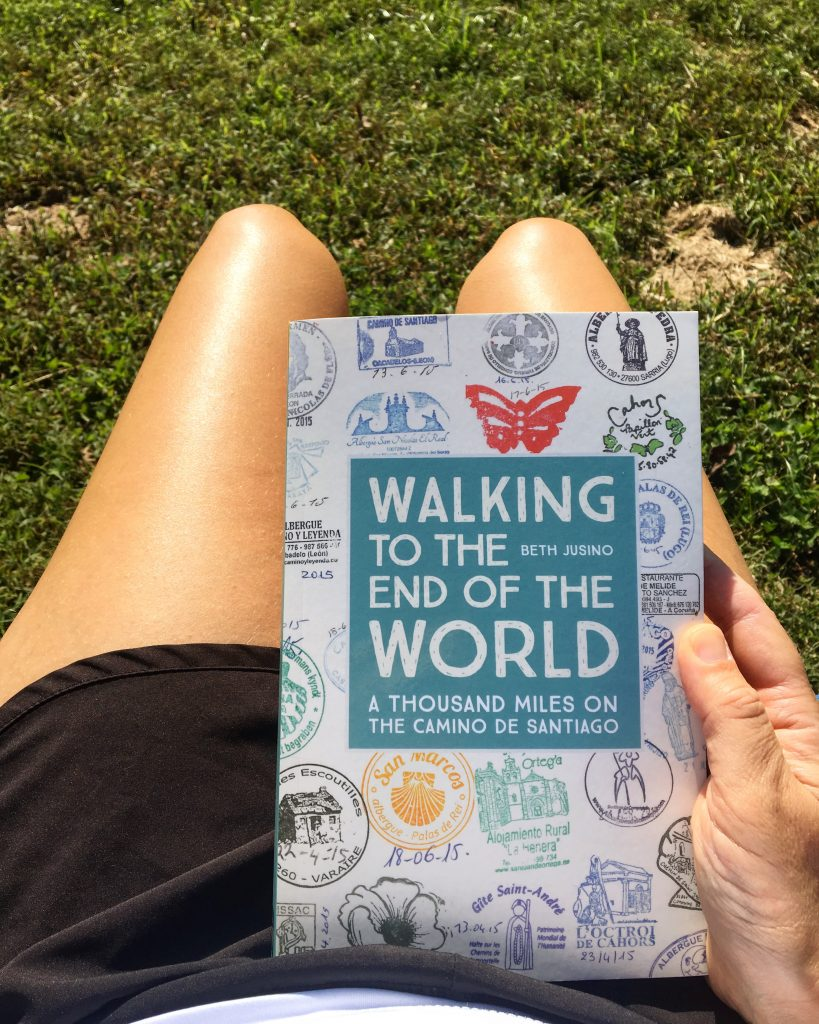 Camino book 'Walking to the End of the World' by Beth Jusino, reading on a summer day