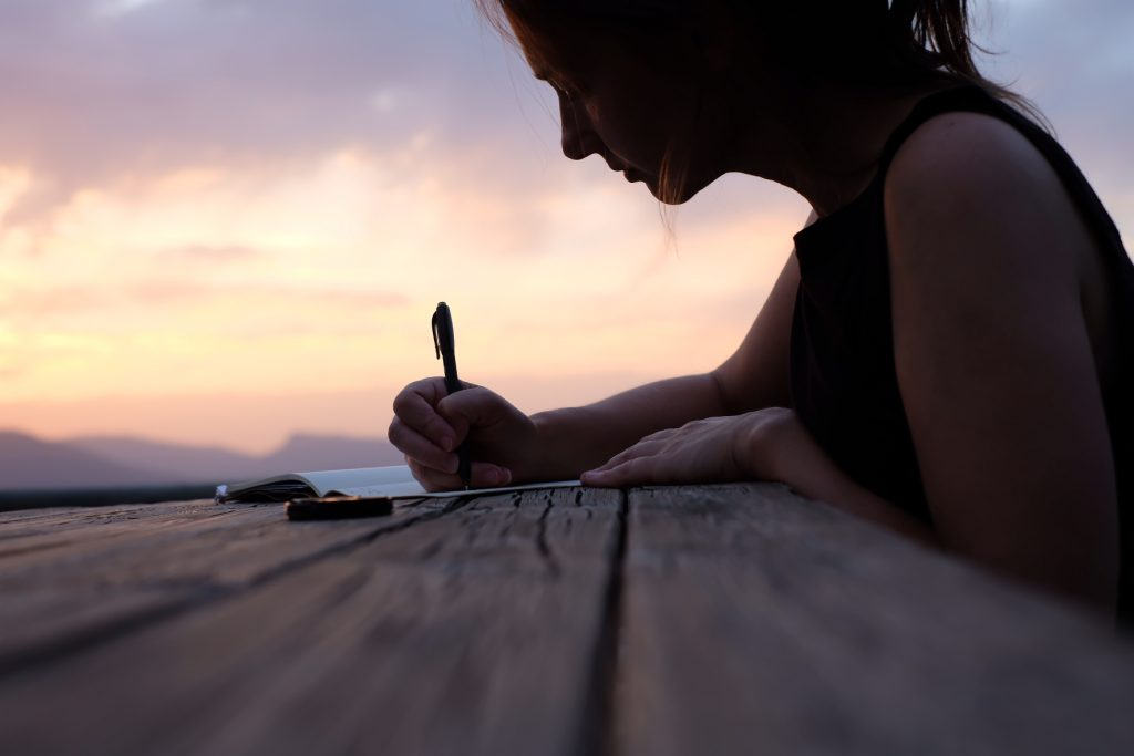Nadine writing in journal in Arrés on the Camino Aragones, sunset in background