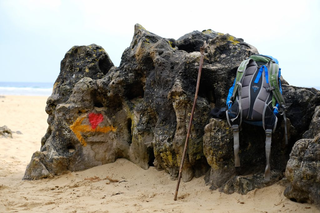 Backpack and walking stick on the beach, Camino del Norte